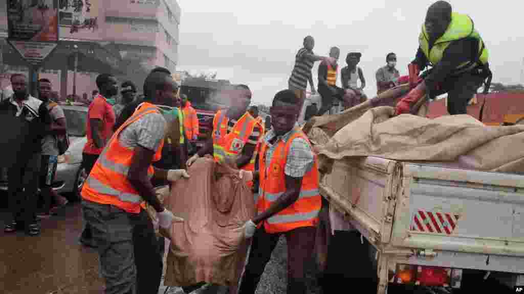 Equipas de resgate transportam os restos mortais de uma pessoa na parte atrás de um camião após a explosão de uma bomba de gasolina em Acra, Gana, Quinta-feira, 4 de Junho, 2015