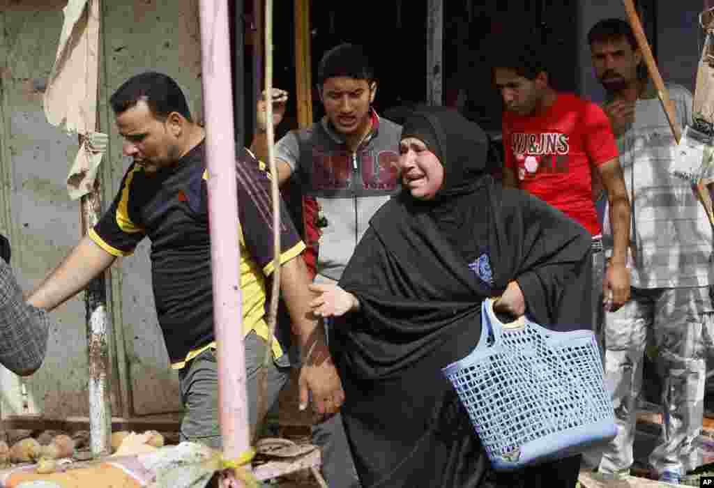 Civilians react at the site of a car bomb attack in front of a crowded popular restaurant in Basra, Iraq, May 20, 2013.