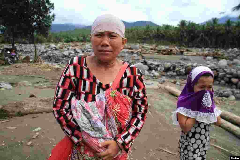 Seorang perempuan Muslim Filipina dan anak perempuannya menangis setelah melihat desanya hancur dilanda banjir bandang akibat badai Tembin di Salvador, Lanao del Norte, Filipina selatan.