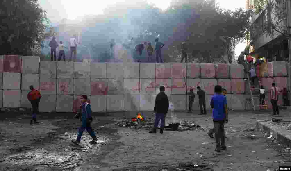 Youths climb a wall that was built by police to prevent clashes between protesters and police at Tahrir Square, Cairo, Egypt, November 29, 2012.