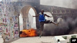 A man jumps during a demonstration in Nigeria's northern city of Kano where running battles broke out between protesters and soldiers on April 18, 2011