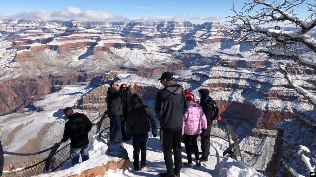 Turistas aprovechan para tomarse fotografías en el Gran Cañón cubierto de nieve, algo poco inusual.