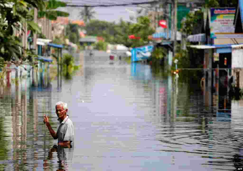 21/10: Một người đàn ông lội qua ngôi làng bị nước lụt cô lập Kajee Nush thuộc tỉnh Pathum Thani gần thủ đô Bangkok của Thái Lan. (REUTERS/Damir Sagolj)