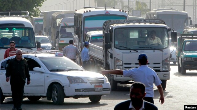 A worker directs vehicles queuing in line at a petrol station, Cairo, March 12, 2013.