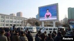 Pxenyanda insanlar küçədə yerləşdirilmiş monitorda nüvə bombasının uğurla sınaqdan keçirildiyi xəbərini dinləyir