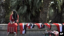 """A young woman sells Egyptian flags in central Cairo. Young activists who spearheaded Egypt's pro-democracy revolution called for a """"no"""" vote in next weekend's referendum on constitutional reform, March 14, 2011"""