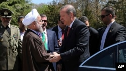 In this photo released by the official website of the office of the Iranian Presidency, Iran's President Hassan Rouhani, left, shakes hand with his Turkish counterpart Recep Tayyip Erdogan during a welcoming ceremony for him at the Saadabad palace in Tehr