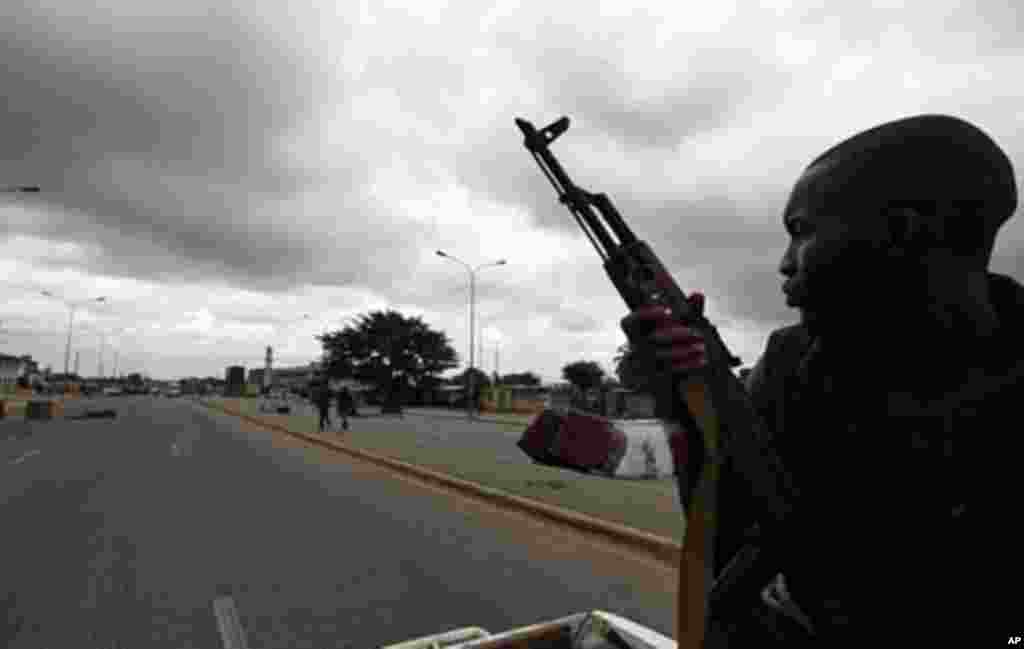 "A pro-Ouattara fighter from a group which calls itself the ""invisible commandos"" patrols a street in northern Abidjan's Abobo district (Mar 26 2011"