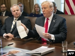 FILE- US President Donald Trump shows a letter he said was from North Korean leader Kim Jong-un during a Cabinet meeting at the White House in Washington, DC, on January 2, 2019.