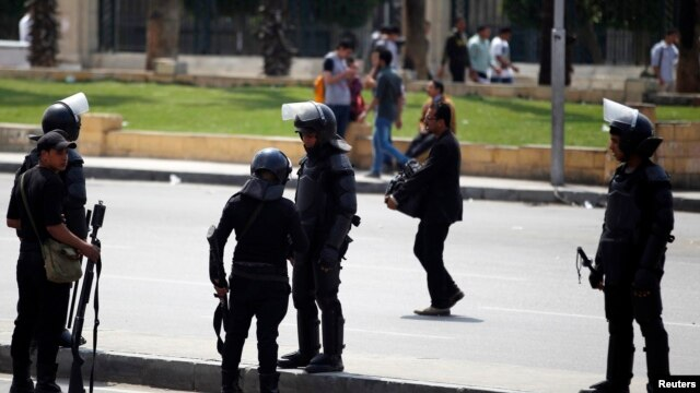 Riot police take their positions near the site of a series of explosions in front of Cairo University April 2, 2014