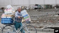 A Sendai resident carries paper goods on a debris-filled street, March 14, 2011