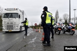 French police officers provide security as they control the crossing of vehicles on the Belgium border between the two countries, following the deadly Paris attacks, in Crespin, France, Nov. 14, 2015.