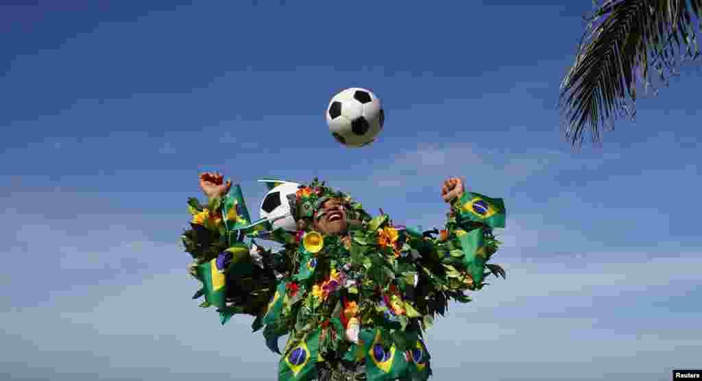 Braziliyalik futbol ishqibozi to'p bilan o'ynamoqda, Rio-de-Janeyro, 8-iyun, 2014-yil.