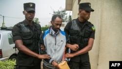 Callixte Nsabimana (C), porte-parole du groupe rebelle du Front de libération nationale (FLN), est escorté par des policiers au tribunal de première instance de Gasabo à Kigali le 23 mai 2019.