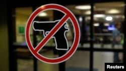 Tanda larangan membawa senjata api di luar sebuah hotel di Sikeston, Missouri, 17 Mei 2018. (Foto: Reuters)