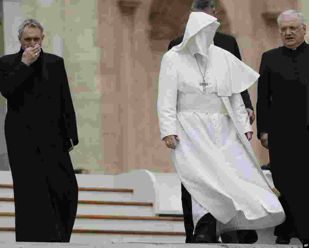 A gust of wind messes up Pope Francis' cape as he leaves with Monsignor Leonardo Sapienza and Archbishop Georg Ganswein at the end of his weekly general audience in St. Peter Square at the Vatican.