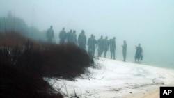 Personal militar busca restos humanos en la playa en medio de la densa niebla, cerca de la base Eglin en Florida.