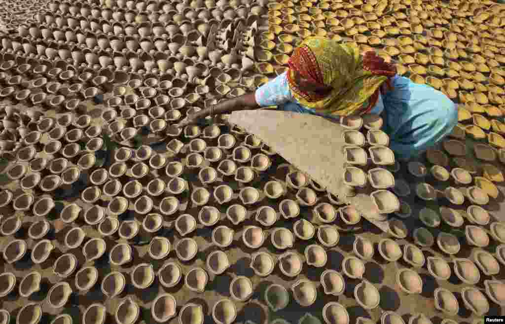 A woman puts out earthen lamps to dry in the sun at her workshop ahead of the Hindu festival of Diwali in the northern Indian city of Chandigarh.