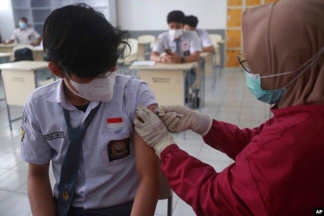 Vaksinasi COVID-19 Sinovac untuk siswa usia 12-17 tahun di Medan, Sumatera Utara, 12 Agustus 2021. (AP Photo/Binsar Bakkara)