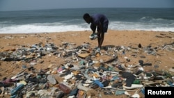 Ivorian painter Aristide Kouame 26, who paints optical effects artworks with worn soles, picks up used flip-flops among the garbage on a beach in Abidjan, Ivory Coast August 2, 2021. (REUTERS/Luc Gnago)