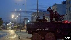 Anggota Pengawal Nasional Tunisia duduk di atas kendaraan lapis baja mereka di tengah bentrokan dengan demonstran menyusul protes di lingkungan Ettadhamen, ibu kota Tunis, 17 Januari 2021. (Foto: dok). Empat tentara dilaporkan tewas akibat ranjau darat (3/2).