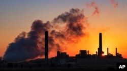 FILE - In this July 27, 2018 photo, Dave Johnson coal-fired power plant is silhouetted against the morning sun in Glenrock, Wyo. (AP Photo/J. David Ake)