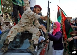 FILE - Libyan revolutionary fighter returning from Sirte is welcomed at Al Guwarsha gate in Benghazi, Libya, Oct. 22, 2011.