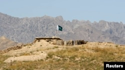 FILE - A Pakistani flag flies on top of a Pakistani check point at the Goshta district of Nangarhar province, where Afghanistan shares a border with Pakistan, May 2, 2013.