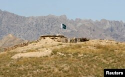 FILE - A Pakistani flag flies on top of a Pakistani check post at the Goshta district of Nangarhar province, where Afghanistan shares borders with Pakistan, May 2, 2013.