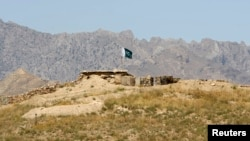 FILE - A Pakistani flag flies on top of a Pakistani check post at the Goshta district of Nangarhar province, where Afghanistan shares borders with Pakistan.