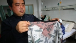 Man displays a blood stained coat in a hospital after his son was stabbed during a knife attack that took place on December 14, 2012 at a primary school in Guangshan county, central China's Henan province.