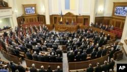 Para anggota parlemen Ukraina mengheningkan cipta untuk menghormati para demonstran yang tewas dalam unjuk rasa di Kyiv, Ukraina (28/1). (AP/Efrem Lukatsky)