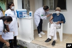 Aloysio Zaluar, 84, is injected with a dose of the Pfizer COVID-19 vaccine during a booster shot campaign for elderly residents in long-term care institutions in Rio de Janeiro, Brazil, Sept. 1, 2021.
