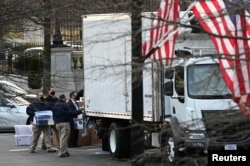 Workers move boxes from the Eisenhower Executive Office Building into a truck on the White House grounds in Washington, U.S., January 14, 2021. (REUTERS/Erin Scott)