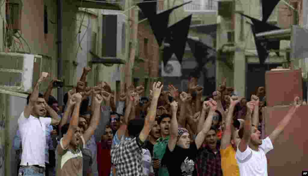 Protestantes contra el régimen gritan mensajes, mientras los nerviosos dueños de tiendas cierran sus ventanas y puertas. Autoridades en la capital intentan aplacar la amenaza cada vez mayor de ensombrecer el regreso de la Fórmul
