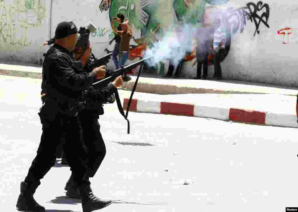 Police officers fire tear gas to break up a protest in the city of Kairouan, Tunisia. Supporters of the hardline Islamist group Ansar al-Sharia clashed with police after the government banned its annual rally, saying it posed a threat to society.
