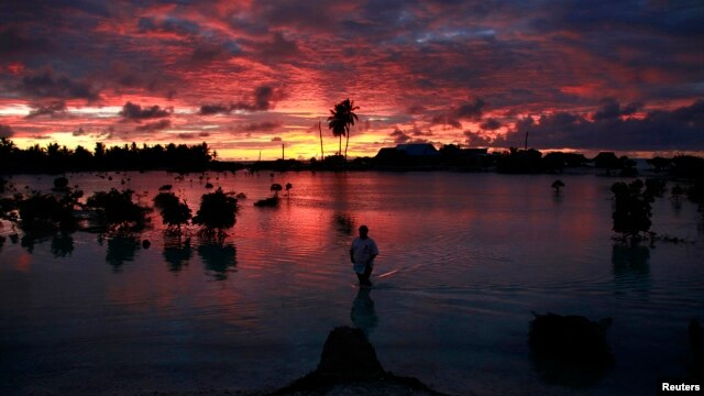 A villager wades through a small lagoon, which at high-tide laps at the base of homes, near the village of Tangintebu on South Tarawa in the central Pacific island nation of Kiribati,  which consists of a chain of 33 atolls and islands that stand just met