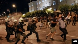 Greek riot police officers charge protesters at Syntagma square in front of the Greek Parliament in central Athens, during minor scuffles following a peaceful ongoing rally against plans for new austerity measures, June 22, 2011
