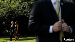 FILE - A Secret Service agent stands in the foreground as President Donald Trump and first lady Melania Trump depart for a weekend retreat at Camp David, from the White House in Washington, Sept. 8, 2017.