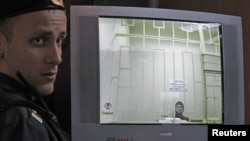 A bailiff stands next to a screen with a live broadcast of opposition activist Leonid Razvozzhayev's appeal at a Moscow court hearing, November 7, 2012.