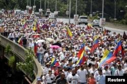 ບັນດາຜູ້ສະໜັບສະໜູນພັກຝ່າຍຄ້ານ ເຂົ້າຮ່ວມໃນການຊຸມນຸມເດີນຂະບວນ ເພື່ອຮຽກຮ້ອງໃຫ້ມີ ການລົງປະຊາມະຕິດ ເພື່ອເຄື່ອນຍ້າຍປະທານາທິບໍດີ Nicolas Maduro ອອກຈາກຕຳແໜ່ງ ໃນນະຄອນຫຼວງ Caracas. 22 ຕຸລາ 2016.