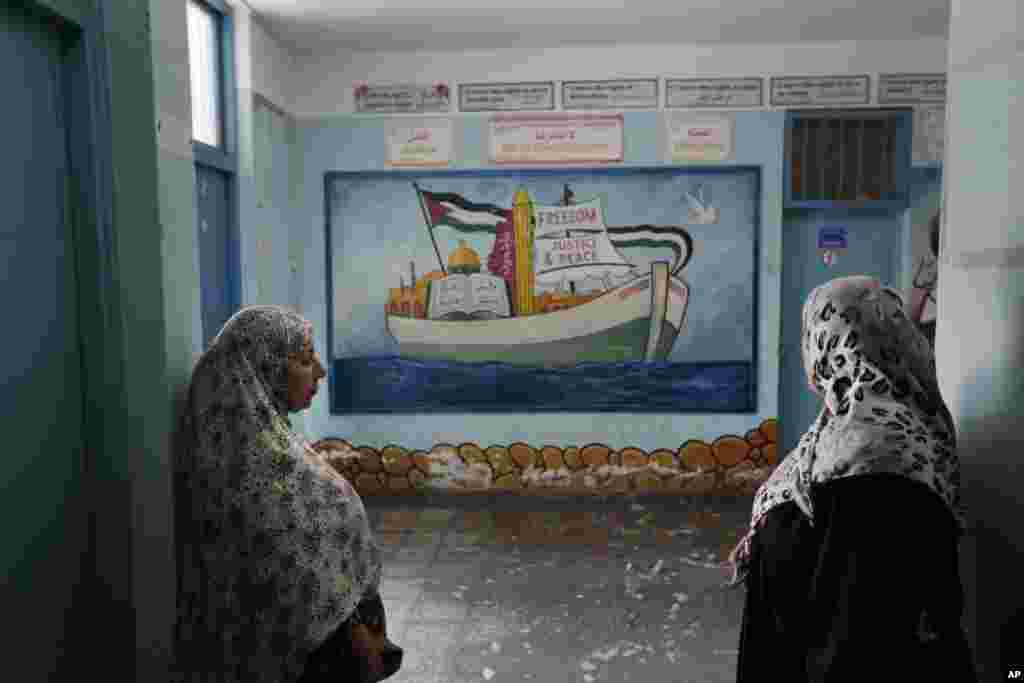 Displaced Palestinians stand in the hallway of a U.N. school where families are taking refuge during the war, in Gaza City, Gaza Strip.