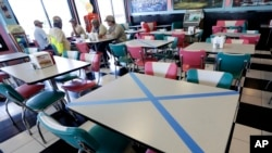 Tables are marked off for social distancing at Hwy 55 Burgers Shakes & Fries Monday, April 27, 2020, in Nolensville, Tenn. Monday is the first day Tennessee restaurants can reopen with reduced seating and social distancing during the coronavirus…