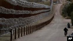 미국 애리조나주와 멕시코에 걸쳐 있는 도시 노갈레스에 세워진 장벽 옆으로 한 소년이 자전거를 타고 있다.