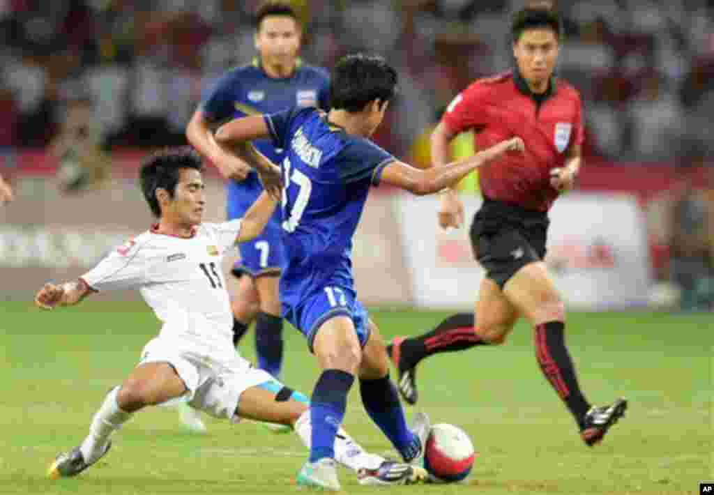 Hein Thiha Zaw of Myanmar, left, is tackled by Tanaboon Kesarat of Thailand, centre, during the soccer final at the SEA Games in Singapore, Monday, June 15, 2015. (AP Photo/Joseph Nair)