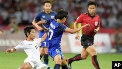 Hein Thiha Zaw dari Myanmar, kiri, dijegal oleh Tanaboon Kesarat dari Thailand, tengah, pada pertandingan final sepakbola SEA Games di Singapura, Senin (15/6).