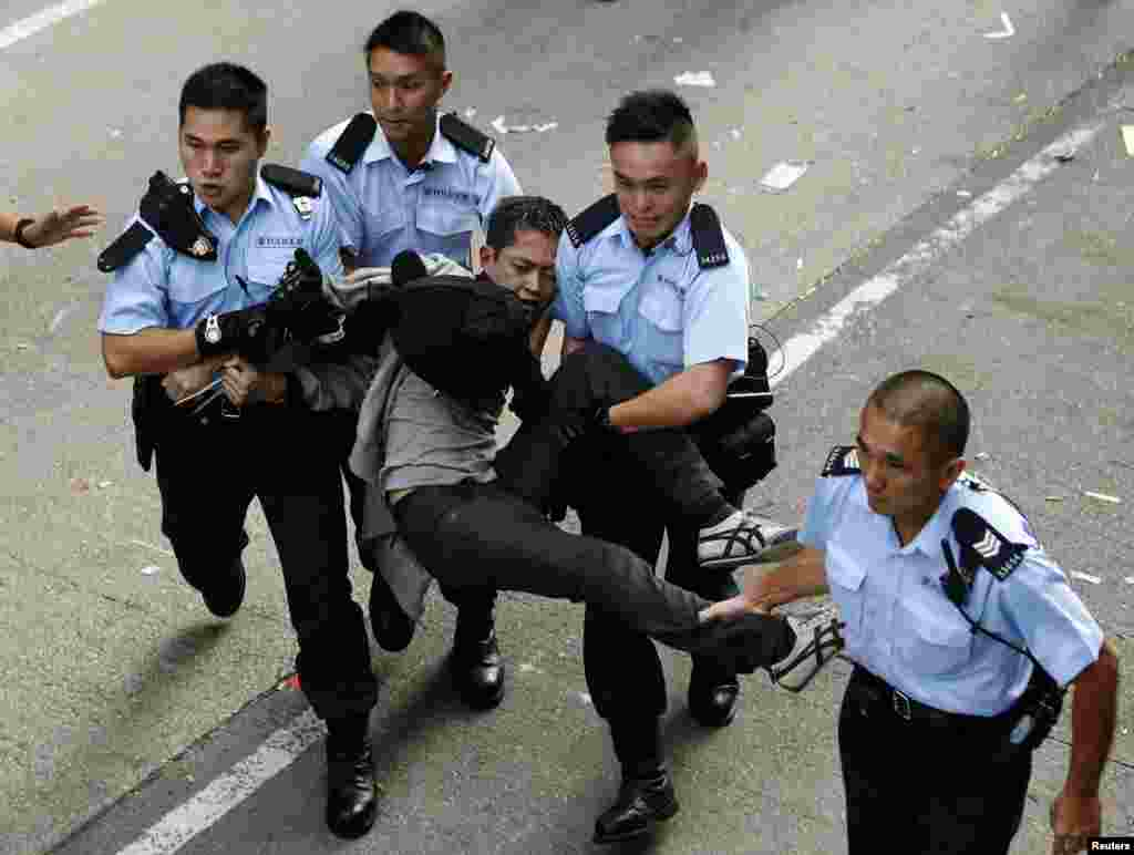 A pro-democracy protester is arrested after refusing to leave the protest site being dismantled by bailiffs under a court injunction, at Mong Kok shopping district in Hong Kong, Nov. 25, 2014.