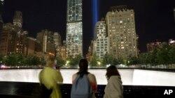ara pengunjung ke Memorial Nasional 11 September menonton instalasi seni yang terdiri dari 88 lampu sebagai bagian dari peringatan serangan 11 September 2001 (8/9). (AP/Mark Lennihan)