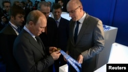 Russia's President Vladimir Putin (front L), International Olympic Committee (IOC) President Jacques Rogge (C) and head of the Sochi 2014 Organising Committee Dmitry Chernyshenko (front R) visit the stand displaying medals for the 2014 Winter Olympic Game