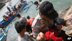Seorang polisi menggendong seorang anak perempuan yang pingsan setelah kapal pencari suaka yang ditumpanginya tenggelam di lepas pantai pulau Jawa di Cianjur, Jawa Barat, Rabu (24/7). Hingga hari ini, jumlah korban dilaporkan telah mencapai 15 orang.